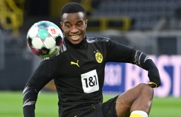 (FILES) In this file photo taken on December 12, 2020 Dortmund's German forward Youssoufa Moukoko warms up on the ball prior the German first division Bundesliga football match BVB Borussia Dortmund v VfB Stuttgart at the Signal Iduna Park Stadium in Dortmund, western Germany. - Borussia Dortmund's Bundesliga title aspirations suffered a fresh dent on December 18, 2020 as they crashed to a 2-1 defeat at Union Berlin on the night their striker Youssoufa Moukoko became the league's youngest ever goalscorer. (Photo by Ina FASSBENDER / various sources / AFP) / DFL REGULATIONS PROHIBIT ANY USE OF PHOTOGRAPHS AS IMAGE SEQUENCES AND/OR QUASI-VIDEO