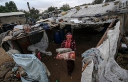 A Palestinian woman carries well cushions outside her makeshift home in the Araiba refugee camp on rainy day, in Rafah in the southern Gaza Strip, on December 16, 2020. (Photo by SAID KHATIB / AFP)