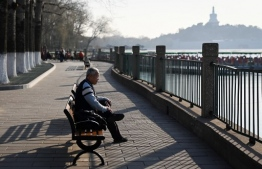 An elderly man takes a rest on a bench at a park in Beijing on December 22, 2020. (Photo by WANG Zhao / AFP)