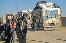 Syrians wait to leave the Kurdish-run al-Hol camp which holds relatives of alleged Islamic State (IS) group fighters, in the Syrian northeastern al-Hasakeh governorate on December 10, 2020. - Al-Hol hosts more than 60,000 people, including 24,300 Syrians either captured or displaced by fighting to expel IS from their last scrap of Syrian territory almost two years ago, according to the UN Office for the Coordination of Humanitarian Affairs. (Photo by Delil SOULEIMAN / AFP)