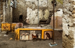 """This picture released on December 26, 2020 by the Pompei Press Office shows a thermopolium, a sort of street """"fast-food"""" counter in ancient Rome, that has been unearthed in Pompei, decorated with polychrome motifs and in an exceptional state of preservation. - The counter frozen by volcanic ash had been partly unearthed in 2019 but the work was extended to best preserve the entire site, located at the crossroads of rue des Noces d'Argent and rue des Balcons. (Photo by Luigi Spina / AFP) / RESTRICTED TO EDITORIAL USE - MANDATORY CREDIT """"AFP PHOTO / POMPEI PRESS OFFICE"""" - NO MARKETING NO ADVERTISING CAMPAIGNS - DISTRIBUTED AS A SERVICE TO CLIENTS"""