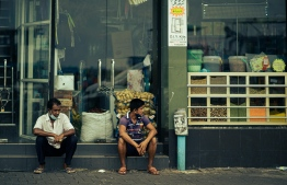 Workers maintain social distancing as they take a break outside a grocery shop. PHOTO/PUBLICITY BUREAU