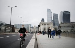 "A cyclist wearing a protective face covering to combat the spread of the coronavirus, rides over London Bridge with buildings in the City of London seen behind in London on December 29, 2020, as Londoners continue to live under Tier 4 lockdown restrictions. - England is ""back in the eye"" of the coronavirus storm, health chiefs warned Tuesday, with as many patients in hospital as during the initial peak in April. (Photo by Tolga Akmen / AFP)"