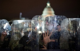 National Guard troops are seen behind shields as they clear a street from protestors outside the Capitol building on January 6, 2021 in Washington, DC. - Donald Trump's supporters stormed a session of Congress held today, January 6, to certify Joe Biden's election win, triggering unprecedented chaos and violence at the heart of American democracy and accusations the president was attempting a coup. (Photo by ROBERTO SCHMIDT / AFP)