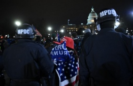 Trump supporters repelled by police officers as a curfew is in order, outside the US Capitol in Washington, DC on January 6, 2021. - Trump supporters remain outside, defying a 6.00 pm (2300 GMT) curfew imposed across the city by Mayor Muriel Bowser. Donald Trump's supporters stormed a session of Congress held today, January 6, to certify Joe Biden's election win, triggering unprecedented chaos and violence at the heart of American democracy and accusations the president was attempting a coup. (Photo by Brendan SMIALOWSKI / AFP)