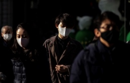 People wearing face masks walk on the street in the Ginza district in Tokyo on January 7, 2021, as Japan's government was expected to declare a coronavirus state of emergency in the greater Tokyo as local media said the capital would again report a record daily number of infections. (Photo by Philip FONG / AFP)