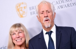 """(FILES) In this file photo English director Michael Apted and his wife Paige Simpson arrive for the 2019 British Academy Britannia (BAFTA) awards at the Beverly Hilton hotel in Beverly Hills on October 25, 2019. - British director Michael Apted, best known for the generation-spanning TV documentary series """"Up"""" and a 1990s James Bond film, died on January 8 at the age of 79, an industry group said. He directed many films, including 1980's """"Coal Miner's Daughter"""", 1988's """"Gorillas in the Mist"""" and the 1998 Bond film """"The World is Not Enough"""". (Photo by VALERIE MACON / AFP)"""