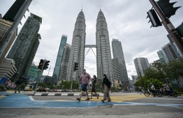 Pedestrians cross a road in front of Malaysia's landmark Petronas Twin Towers in Kuala Lumpur on January 12, 2021, as Malaysian authorities were set to impose tighter restrictions to try to halt the spread of the Covid-19 coronavirus. Mohd RASFAN / AFP