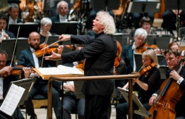 (FILES) This file photo taken on September 14, 2017 shows the London Symphony Orchestra's Music Director Simon Rattle conducting the LSO playing at The Barbican in London. Simon Rattle, one of the most renowned musicians in the world, will leave his leading post at the London Symphony Orchestra to take on the chief conductor job at the Bavarian Radio Symphony Orchestra in Munich, southern Germany, from 2023, it was announced on January 11, 2021.