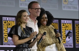 "(FILES) In this file photo taken on July 20, 2019 (FromL) US actress Elizabeth Olsen, English-US actor Paul Bethany and US actress Teyonah Parris speak on stage for the Marvel panel in Hall H of the Convention Center during Comic Con in San Diego, California. - When the Marvel superhero movies reached their box office-shattering climax in 2019, nobody could have predicted the saga's next installment would be a kitsch, black-and-white TV sitcom called ""WandaVision."" But a lot has changed since Iron Man and friends saved the world in that summer's all-time record-grossing blockbuster ""Avengers: Endgame"" (and mopped up some loose plot points in ""Spider-Man: Far From Home"" shortly thereafter.) The wildly popular franchise of 23 interconnected movies has ground to a halt along with the rest of the world as Covid-19 shuttered movie theaters, delaying ""Black Widow"" and other big-screen superhero sequels. (Photo by Chris Delmas / AFP)"