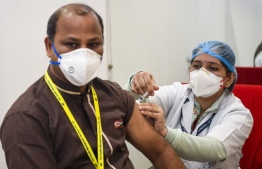 A medical worker inoculates a colleague with a Covid-19 coronavirus vaccine at a hospital in New Delhi on January 16, 2021. (Photo by Prakash SINGH / AFP)