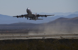 "The Virgin Orbit ""Cosmic Girl"" - a modified Boeing Co. 747-400 carrying a LauncherOne rocket under it's wing - takes off for the Launch Demo 2 mission from Mojave Air and Space Port on January 17, 2021 in Mojave, California. - The LauncherOne rocket, which will release from the wing of the Boeing 747 before ignition, contains small research satellites, known as CubeSats for NASA's Educational Launch of Nanosatellites (ELaNa) 20 mission developed by nine research universities and a NASA center. (Photo by Patrick T. FALLON / AFP)"