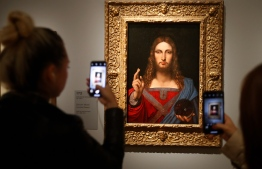 "(FILES) In this file photograph taken on October 22, 2019, visotors take photographs with mobile phone of the oil painting by Leonardo da Vinci "" Salvator Mundi"", during the opening of the exhibition "" Leonardo da Vinci "" at The Louvre Museum in Paris. - Italian police has found a 500-year-old copy of Leonardo da Vinci's Salvator Mundi in a Naples flat and returned it to a museum that had no idea it had been stolen. Officers said late January 18, 2021, that they had arrested the 36-year-old owner of the apartment on suspicion of receiving stolen goods, after the painting was found in his bedroom cupboard. (Photo by FRANCOIS GUILLOT / AFP) /"