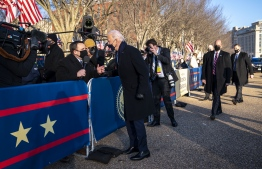 US President Joe Biden talks with NBC Reporter Mike Memoli  as he and First Lady Dr. Jill Biden walk along Pennsylvania Avenue in front of the White House during Inaugural celebrations, January 20, 2021. (Photo by Doug Mills / POOL / AFP)