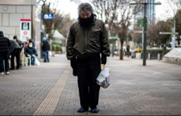 "This picture taken on January 9, 2021 shows a man who identified himself as ""Yuichiro"" holding a bag of food distributed by non-profit organization Moyai Support Centre for Independent Living, in the Shinjuku district of Tokyo. - While Japan has seen a comparatively small coronavirus outbreak, with around 4,500 deaths so far, and avoided the harsh lockdowns seen in other countries, poverty campaigners say the most vulnerable are being hit hard. (Photo by Philip FONG / AFP) /"