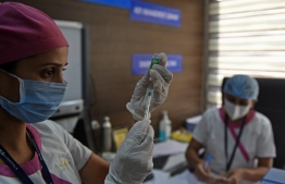 A medical worker fills a syringe with Covishield, AstraZeneca-Oxford's Covid-19 coronavirus vaccine made by India's Serum Institute, at a hospital in Ahmedabad on January 21, 2021. (Photo by Sam PANTHAKY / AFP)