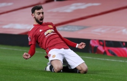 Manchester United's Portuguese midfielder Bruno Fernandes celebrates scoring his team's third goal during the English FA Cup fourth round football match between Manchester United and Liverpool at Old Trafford in Manchester, north west England, on January 24, 2021. (Photo by Martin Rickett / POOL / AFP) / RESTRICTED TO EDITORIAL USE. No use with unauthorized audio, video, data, fixture lists, club/league logos or 'live' services. Online in-match use limited to 120 images. An additional 40 images may be used in extra time. No video emulation. Social media in-match use limited to 120 images. An additional 40 images may be used in extra time. No use in betting publications, games or single club/league/player publications. /