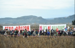 """Activists of the Attac association gather in front of banners reading """"Stop Amazon"""" and """"Neither here nor elsewhere"""", during a demonstration on the site where Amazon plans to build a 38.800 square metres warehouse, in Fournes, southeastern France on January 30, 2021. (Photo by Sylvain THOMAS / AFP)"""