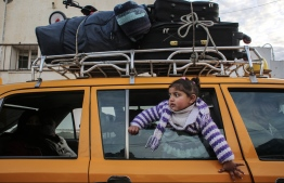 """A girl looks on through the window of a vehicle whose top is loaded with suitcases, while waiting at the Rafah border crossing's departure area to travel from the Gaza Strip into Egypt, on February 9, 2021, which reopened after an Egyptian announcement to let through incoming traffic until further notice. - Egypt on February 9 opened its border crossing """"indefinitely"""" with Gaza -- the Israeli-blockaded Palestinian enclave -- against the backdrop of Palestinian political unity talks in Cairo continue, a security source said. (Photo by SAID KHATIB / AFP)"""