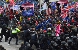 (FILES) In this file photo taken on January 06, 2021 Trump supporters clash with police and security forces as they push barricades to storm the US Capitol in Washington D.C. - Impeachment prosecutors aired terrifying, never-before-seen footage of senior US politicians fleeing for their lives during the January assault on Congress by Donald Trump supporters on day two of the former president's Senate trial. With painstaking, graphic presentations, Democratic impeachment managers walked senators through hours of video, some of which came from security cameras and police bodycams and was being aired for the first time. (Photo by ROBERTO SCHMIDT / AFP)