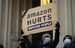 (FILES) In this file photo Amazon workers and community allies demonstrate during a protest organized by New York Communities for Change and Make the Road New York in front of the Jeff Bezos' Manhattan residence in New York on December 2, 2020. - New York state's attorney general on February 17, 2021 sued Amazon, claiming the e-commerce giant failed to adequately protect its warehouse workers from risks during the Covid-19 pandemic. The move comes days after Amazon filed its own legal action seeking to block New York state Attorney General Letitia James from taking steps to enforce federal workplace safety regulations. (Photo by Kena Betancur / AFP)