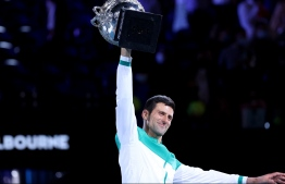 Serbia's Novak Djokovic celebrates after winning against Russia's Daniil Medvedev in their men's singles final match on day fourteen of the Australian Open tennis tournament in Melbourne on February 21, 2021. (Photo by David Gray / AFP) /