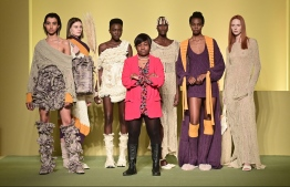 "Cameroonian fashion stylist Claudia Gisele Ntsama (C) from the collective ""Black Lives Matter in Italian Fashion"" poses with her models on February 17, 2021 in Milan during the filming of the fashion show that will open the Milan Fashion Week on February 24, 2021. After a years-long battle to improve diversity on the Italian catwalks, a group of five black designers made their on-schedule debut on February 24, 2021 by opening the women's Fall/Winter fashion shows. MIGUEL MEDINA / AFP"