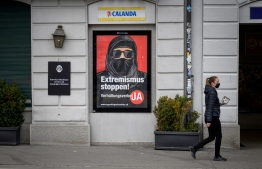 "A woman wearing a protective facemask, as a preventive measure against the Covid-19 (the novel coronavirus), walks past a campaign poster, in favour of the ""burqa ban"" initiative reading in German: ""Stop extremism!"" on March 3, 2021 in the streets of Zurich, ahead of a nationwide vote on March 7, 2021 by Swiss citizen on whether to ban full facial coverings in public places. - Polls indicate a majority support the move, in a vote that comes after years of debate following similar bans in other European countries -- and in some Muslim-majority states. (Photo by Fabrice COFFRINI / AFP)"
