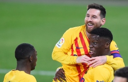 Barcelona's Spanish midfielder Ilaix Moriba (R) celebrates with Barcelona's Argentinian forward Lionel Messi and Barcelona's French forward Ousmane Dembele after scoring during the Spanish League football match between CA Osasuna and FC Barcelona at El Sadar stadium in Pamplona on March 6, 2021. (Photo by ANDER GILLENEA / AFP)