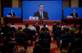 Chinese Foreign Minister Wang Yi speaks via live video transmission during a press conference at the National People's Congress in Beijing on March 7, 2021. PHOTO: Noel Celis / AFP