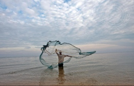 Fisherman along the Wataboo beach casts net in the water to catch small fish. PHOTO: ESCAP