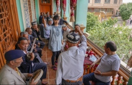 Tourists and locals enjoy local entertainment at a guesthouse in Kashgar in Xinjiang Uygur Autonomous Region, northwest China, May 17, 2020.