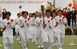 Members of Nadeshiko Japan, Japan's women's national soccer team, lead the torch relay on day one of the torch relay in Naraha, Fukushima Prefecture on March 25, 2021. (Photo by KIM KYUNG-HOON / POOL / AFP)