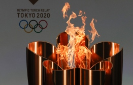 The celebration cauldron is seen lit on the first day of the Tokyo 2020 Olympic torch relay in Naraha, Fukushima prefecture on March 25, 2021. (Photo by KIM KYUNG-HOON / POOL / AFP)