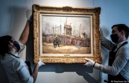 "(FILES) In this file photo taken on February 24, 2021 two employees put on display a painting titled ""Scene de rue a Montmartre"" (Impasse des deux freres et le moulin à Poivre), 1887 by Dutch painter Vincent Van Gogh, at the Sotheby's auction house in Paris on February 24, 2021. One of the few paintings of Vincent Van Gogh still in private hands will be put up for auction on March 25, 2021 in one of the most anticipated sales of modern works this year. ""Street Scene in Montmartre"" is the highlight of 33 works from masters including Degas, Magritte, Modigliani, Klee, Rodin and his muse Camille Claudel being sold in an auction streamed live by Sotheby's in Paris. STEPHANE DE SAKUTIN / AFP"