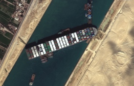 This satellite imagery released by Maxar Technologies shows tug boats and dredgers on March 27, 2021, attempting to free the Taiwan-operated MV Ever Given lodged sideways and impeding all traffic across Egypt's Suez Canal. The container ship, which is longer than four football fields, has been wedged diagonally across the entire canal since March 23, shutting the waterway in both directions. The blockage has caused a huge traffic jam for more than 200 ships at either end of the 193-km (120-mile) long canal and major delays in the delivery of oil and other products. Satellite image ©2021 Maxar Technologies / AFP