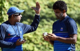 "(FILES) In this file photo taken on March 10, 2015 former Sri Lanka fast bowler and current bowling coach Chaminda Vaas (L) speaks to Thisara Perera during a training session at the Bellerive Oval ground ahead of the 2015 Cricket World Cup Pool A match between Scotland and Sri Lanka in Hobart. - Sri Lanka's fast bowling coach Chaminda Vaas returned to his job a month after quitting over a pay dispute that was ""amicably resolved,"" the cricket board said on March 26, 2021. (Photo by Indranil MUKHERJEE / AFP)"