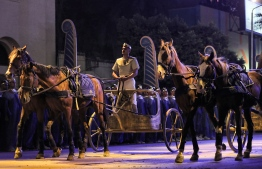 A performer rides a two-horse chariot at the start of the parade of 22 ancient Egyptian royal mummies departing from the Egyptian Museum in Cairo's Tahrir Square on April 3, 2021, on their way to their new resting place at the new National Museum of Egyptian Civilisation (NMEC) about seven kilometres south in historic Fustat (Old Cairo). - Dubbed the Pharaohs' Golden Parade, the 18 kings and four queens will travel in order, oldest first, each aboard a separate float decorated in ancient Egyptian style. (Photo by Mahmoud KHALED / AFP)