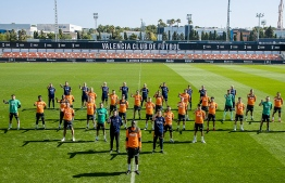 A handout picture released by the Valencia football club shows players and staff showing their support to Valencia's French defender Mouctar Diakhaby (C) as they protest against racism during a training session in Valencia on April 5, 2021. - Valencia's players walked off during their La Liga game with Cadiz on April 4 in protest against racist abuse, with coach Javi Gracia later claiming they were told they would be punished if they refused to resume the match. (Photo by Lazaro DELA PENA / VALENCIA CF / AFP) /