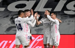 "Real Madrid's French forward Karim Benzema (2R) celebrates with teammates after scoring during the ""El Clasico"" Spanish League football match between Real Madrid CF and FC Barcelona at the Alfredo di Stefano stadium in Valdebebas, on the outskirts of Madrid on April 10, 2021. (Photo by JAVIER SORIANO / AFP)"
