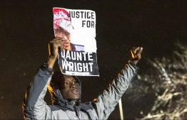 "A demonstrator holds a photo of Daunte Wright and shouts ""Don't shoot"" at the police after curfew as people protest the death of Daunte Wright who was shot and killed by a police officer in Brooklyn Center, Minnesota on April 13, 2021. - Tensions have soared over the death on April 11 of African American Daunte Wright near the Midwestern US city, a community already on edge over the ongoing trial of a policeman accused of killing another Black man, George Floyd. (Photo by Kerem YUCEL / AFP)"