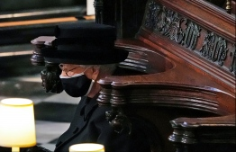 Britain's Queen Elizabeth II sits alone in the quire of St George's Chapel during the funeral service of her husband Britain's Prince Philip, Duke of Edinburgh in Windsor Castle in Windsor, west of London, on April 17, 2021. - Philip, who was married to Queen Elizabeth II for 73 years, died on April 9 aged 99 just weeks after a month-long stay in hospital for treatment to a heart condition and an infection. (Photo by Yui Mok / POOL / AFP)