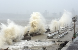 Waves lash over onto a shoreline in Mumbai on May 17, 2021, as Cyclone Tauktae, packing ferocious winds and threatening a destructive storm, surge bore down on India, disrupting the country's response to its devastating Covid-19 outbreak. (Photo by Sujit Jaiswal / AFP)