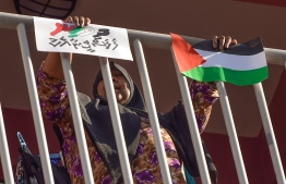 """A woman holding a Palestinian flag and a poster that says """"Maldivians with Palestine,"""" in Dhivehi -- Photo: Nishan Ali/ Mihaaru"""