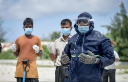 People in PPE, and wearing masks, administering funeral rites to people that have passed away from COVID-19 -- Nishan Ali/ Mihaaru