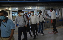 People commute in a metro at a station after the services were allowed to operate at 50 percent capacity in New Delhi on June 7, 2021, as India's capital began a gradual easing of restrictions after Covid-19 coronavirus infections across the country fell to a two-month low -- Photo by Money Sharma/ AFP