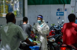 Health worker in PPE collecting random samples in Male' -- Photo: Ahmed Awshan Ilyas/ Mihaaru