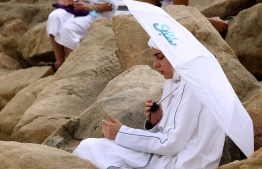 Muslim pilgrims gather around Mount Arafat, also known as Jabal al-Rahma (Mount of Mercy), southeast of the holy city of Mecca, during the climax of the Hajj pilgrimage amid the COVID-19 pandemic, on July 19, 2021. - Muslim pilgrims gathered at Mount Arafat today in the high point of this year's hajj, being held in downsized form and under coronavirus restrictions for the second year running. Just 60,000 people, all citizens or residents of Saudi Arabia, have been selected to take part in this year's hajj, with foreign pilgrims again barred. (Photo by Fayez Nureldine / AFP)