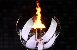 Japanese tennis player Naomi Osaka holds the Olympic Torch after lighting the flame of hope in the Olympic Cauldron during the opening ceremony of the Tokyo 2020 Olympic Games, at the Olympic Stadium, in Tokyo, on July 23, 2021. -- Photo by Jewel SAMAD / AFP