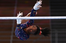 USA's Simone Biles competes in the uneven bars event of the  artistic gymnastics women's qualification during the Tokyo 2020 Olympic Games at the Ariake Gymnastics Centre in Tokyo on July 25, 2021 --  Photo:  Loic Venance/ AFP